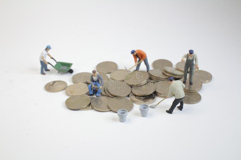 οι μίνι εργαζόμενοι κινούν τα νομίσματα αναπτύσσοντας χρήματα στοκ φωτογραφία με δικαίωμα ελεύθερης χρήσης