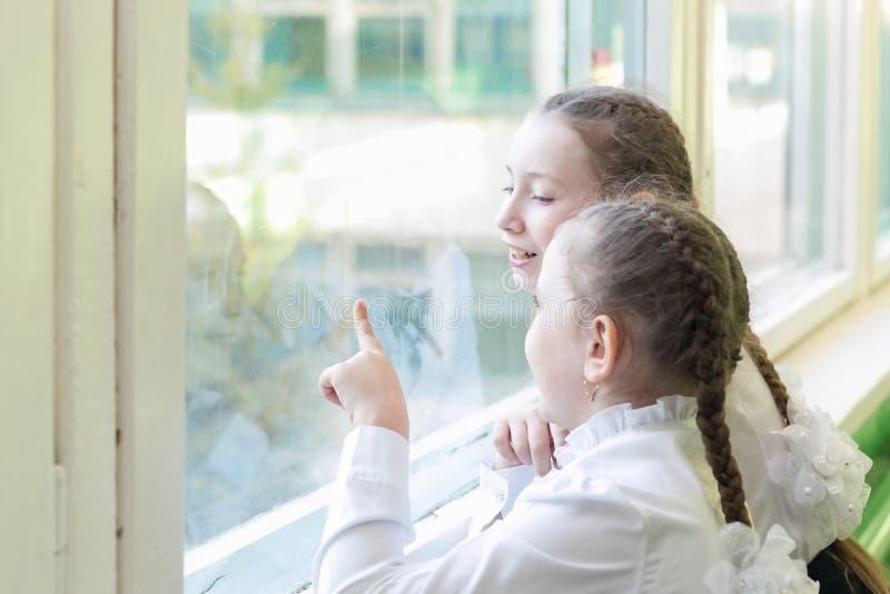 Οι μαθήτριες κοριτσιών φαίνονται έξω το παράθυρο στην οδό στοκ εικόνα