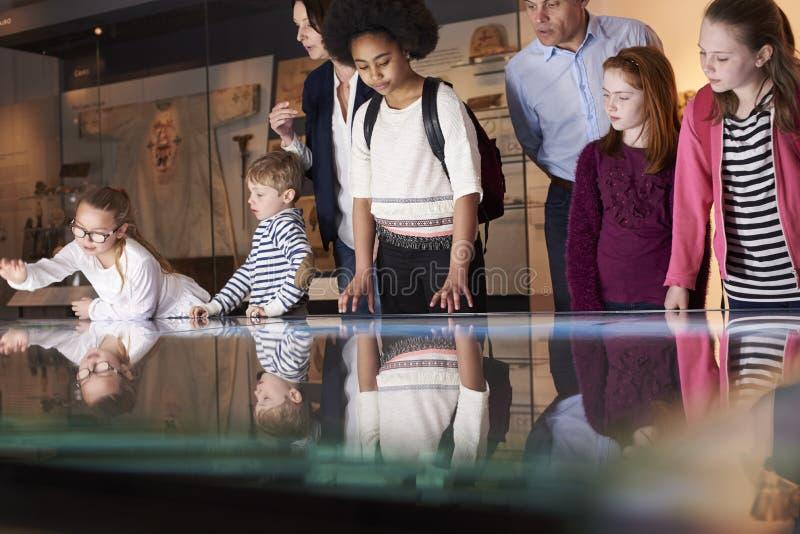 Οι μαθητές στο σχολικό τομέα σκοντάφτουν στο μουσείο εξετάζοντας το χάρτη στοκ εικόνες με δικαίωμα ελεύθερης χρήσης