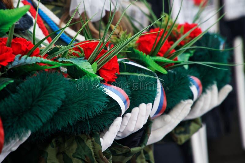 Οι μαθητές στρατιωτικής σχολής κρατούν ένα στεφάνι και τα λουλούδια στη μνήμη εκείνοι που σκοτώνονται στους πολέμους και τις ένοπ στοκ φωτογραφία με δικαίωμα ελεύθερης χρήσης