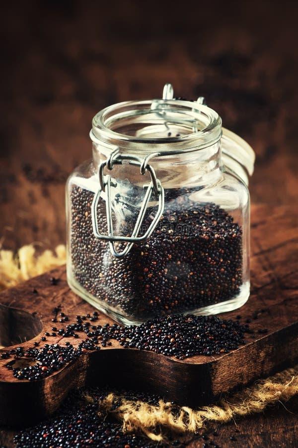 Οι μαύροι quinoa σπόροι έχυσαν από το βάζο γυαλιού, εκλεκτής ποιότητας επιτραπέζιο υπόβαθρο κουζινών, εκλεκτική κάθετη εικόνα εστ στοκ φωτογραφία με δικαίωμα ελεύθερης χρήσης