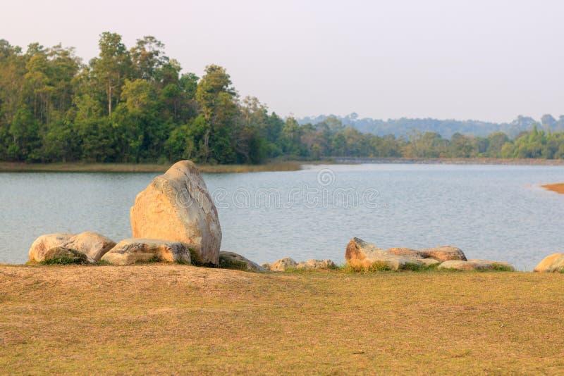 Οι μεγάλοι βράχοι στους πράσινους χορτοτάπητες και μια λίμνη βλέπουν το βράδυ πριν από το s στοκ εικόνες