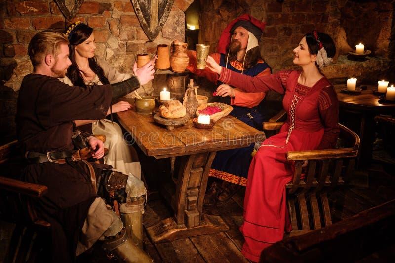 Οι μεσαιωνικοί άνθρωποι τρώνε και πίνουν στην αρχαία ταβέρνα κάστρων στοκ φωτογραφία με δικαίωμα ελεύθερης χρήσης