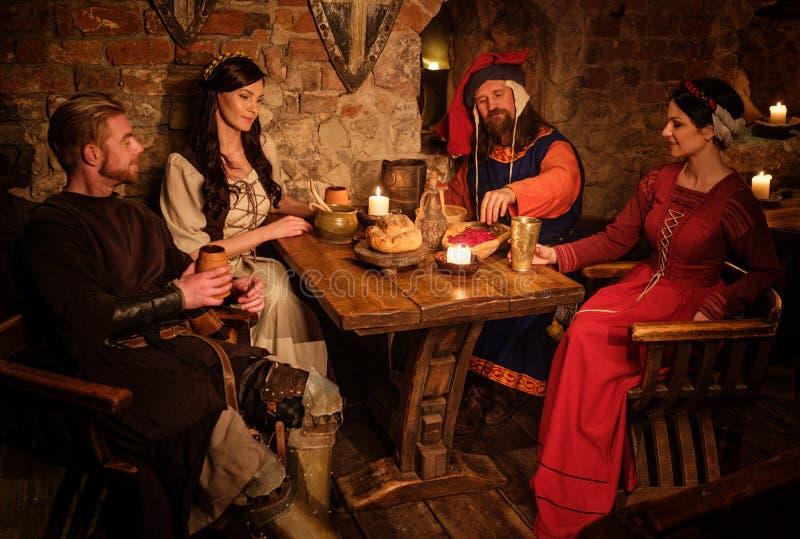 Οι μεσαιωνικοί άνθρωποι τρώνε και πίνουν στην αρχαία ταβέρνα κάστρων στοκ εικόνα με δικαίωμα ελεύθερης χρήσης
