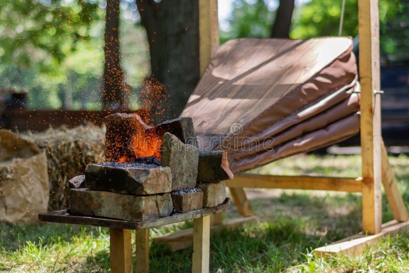Οι μεσαιωνικοί φυσητήρες κάνουν την πυρκαγιά των ανθράκων και των σπινθήρων να πετάξει από τον υπαίθριο σιδηρουργό στοκ εικόνα