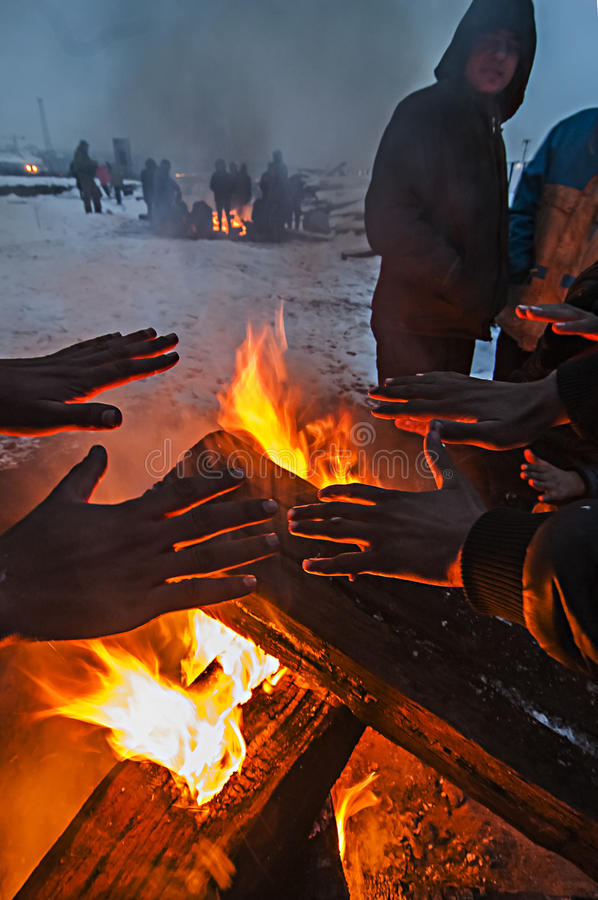 Οι μετανάστες θερμαίνονται πέρα από μια πυρκαγιά στο χιόνι και το κρύο καιρό στοκ φωτογραφία