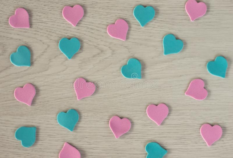 Οι μικρές καρδιές του ρόδινου και μπλε χρώματος βρίσκονται σε έναν άσπρο ξύλινο πίνακα στοκ εικόνες