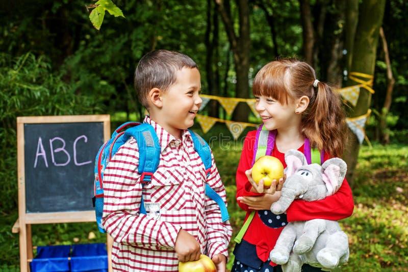 Οι μικροί σπουδαστές μιλούν και γελούν Παιδιά με τα σακίδια πλάτης και appl στοκ εικόνες