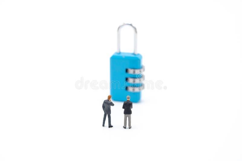 Οι μικροσκοπικοί επιχειρηματίες ανθρώπων αναλύουν τον κωδικό πρόσβασης από το μπλε κλειδί ως επιχειρησιακή έννοια υποβάθρου και έ στοκ φωτογραφία