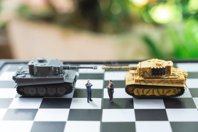Οι μικροσκοπικοί επιχειρηματίες ανθρώπων που στέκονται σε μια σκακιέρα με μια δεξαμενή διαμορφώνουν σύμφωνα με την πίσω διαπραγμά στοκ εικόνες