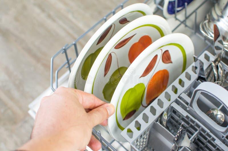 Οι μικροδουλειές, παίρνουν τα καθαρά πιάτα από το πλυντήριο πιάτων στοκ εικόνες