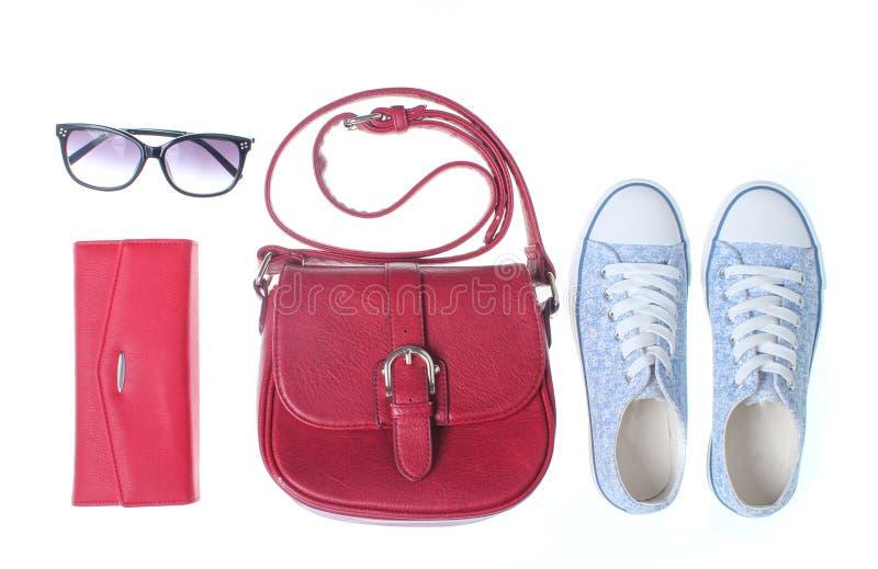 Οι μοντέρνες γυναίκες τοποθετούν σε σάκκο, πορτοφόλι, πάνινα παπούτσια, γυαλιά ηλίου στοκ εικόνα