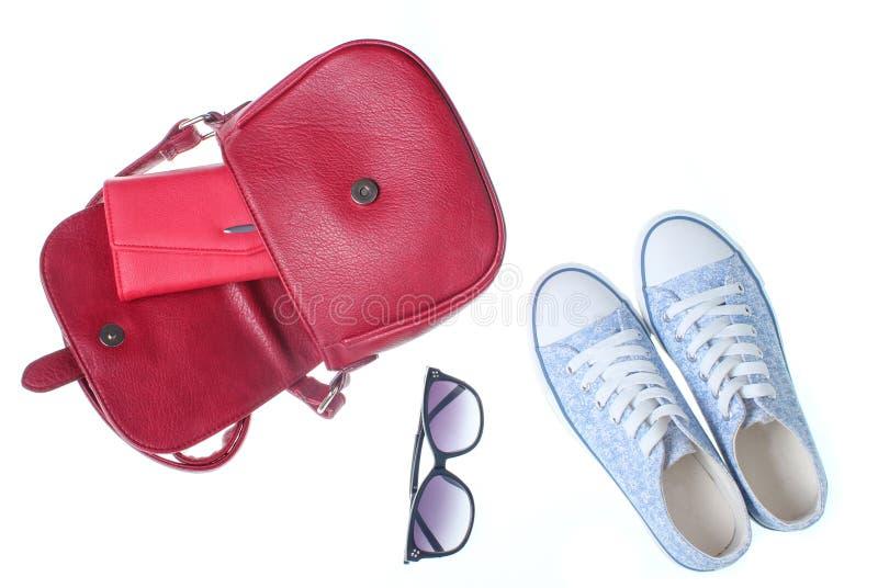 Οι μοντέρνες γυναίκες τοποθετούν σε σάκκο, πορτοφόλι, πάνινα παπούτσια, γυαλιά ηλίου στοκ εικόνες