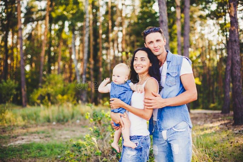 Οι μοντέρνοι όμορφοι μοντέρνοι γονείς κρατούν ένα κορίτσι στο πάρκο στο υπόβαθρο ενός πυκνού δάσους στοκ φωτογραφία
