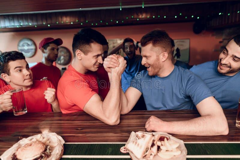 Οι μπλε και κόκκινοι θαυμαστές ομάδων οπλίζουν την πάλη στον αθλητικό φραγμό με τους ανεμιστήρες στο υπόβαθρο στοκ φωτογραφία με δικαίωμα ελεύθερης χρήσης