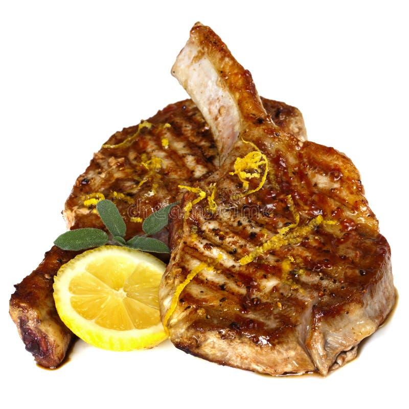 οι μπριζόλες έψησαν το λεμόνι πέρα από το λογικό λευκό χοιρινού κρέατος στη σχάρα στοκ φωτογραφία