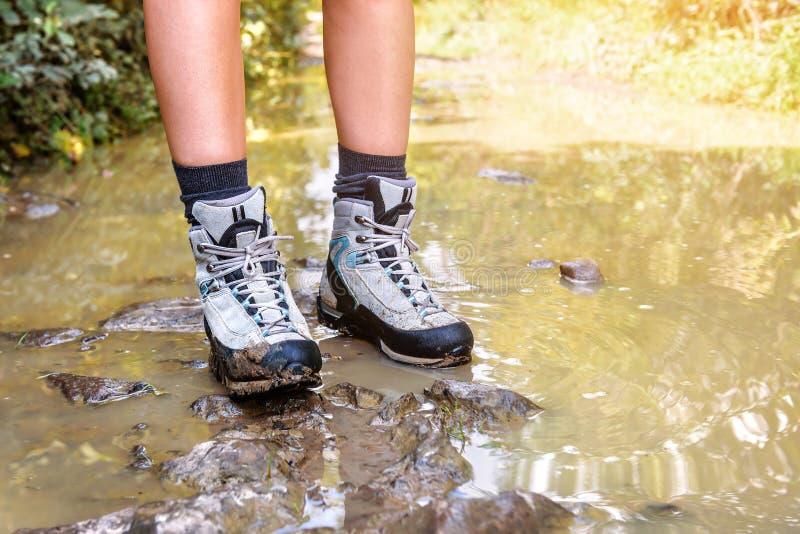 Οι μπότες πεζοπορίας στα πόδια γυναικών στέκονται στο έλος στοκ φωτογραφία