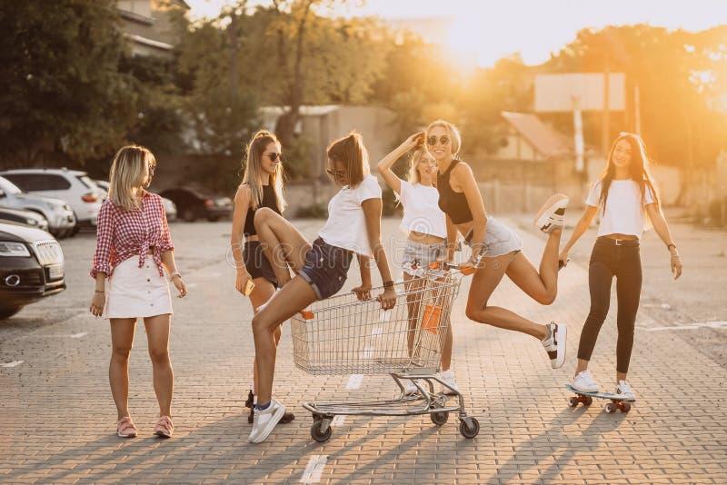 Οι νέες γυναίκες με ένα κάρρο υπεραγορών έχουν τη διασκέδαση στοκ εικόνα με δικαίωμα ελεύθερης χρήσης