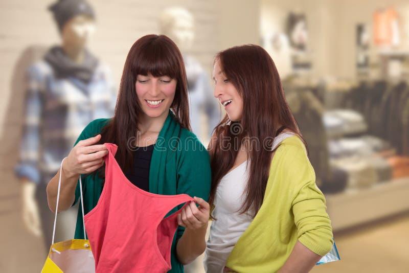 Οι νέες γυναίκες με τις αγορές τοποθετούν τα ενδύματα αγοράς στο κατάστημα ιματισμού σε σάκκο στοκ φωτογραφίες