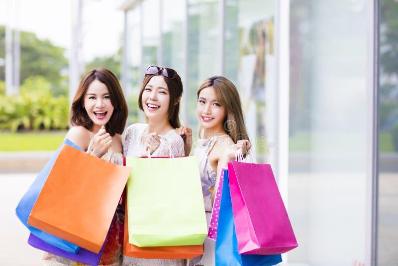 Οι νέες γυναίκες ομαδοποιούν τις φέρνοντας τσάντες αγορών στην οδό στοκ εικόνα