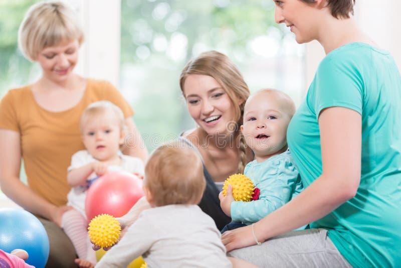 Οι νέες γυναίκες στη μητέρα και το παιδί ομαδοποιούν το παιχνίδι με το μωρό τους ki στοκ εικόνες
