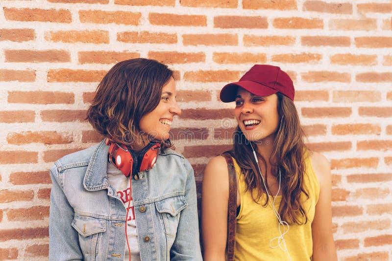 Οι νέες γυναίκες συνδέουν το κοίταγμα και το χαμόγελο της μιας την άλλη σε ένα υπόβαθρο τουβλότοιχος Ίδια ευτυχία φύλων και χαρού στοκ εικόνα