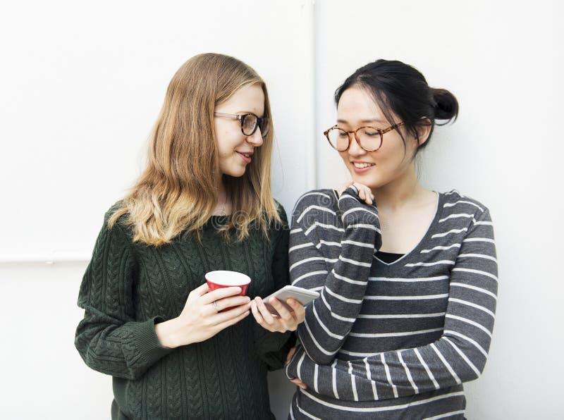 Οι νέες γυναίκες χρησιμοποιούν το κινητό τηλέφωνο στοκ εικόνα