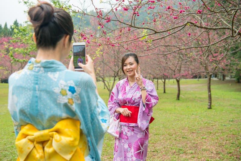 Οι νέες κυρίες βοηθούν η μια την άλλη που παίρνει τις φωτογραφίες στοκ φωτογραφία