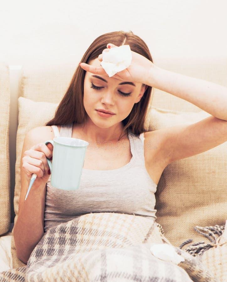 Οι νέοι άρρωστοι γυναικών στο κρεβάτι με τη θερμοκρασία πίνουν καυτό στοκ φωτογραφία