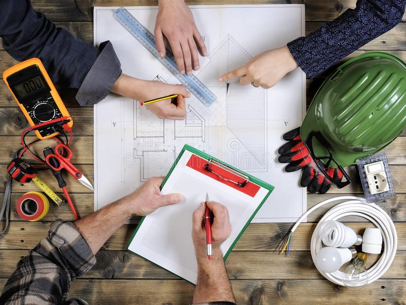 Οι νέοι αρχιτέκτονες και οι τεχνικοί αναλύουν το πρόγραμμα ενός κατοικημένου σπιτιού στοκ εικόνα με δικαίωμα ελεύθερης χρήσης