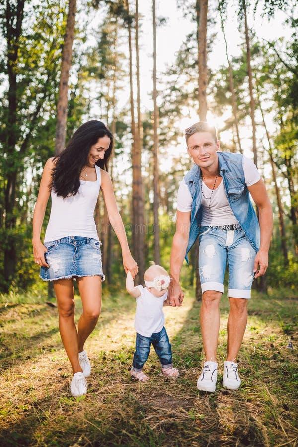 Οι νέοι γονείς διδάσκουν για να περπατήσουν μια κόρη ενός έτους στη φύση σε ένα πάρκο σε έναν χορτοτάπητα Τα πρώτα βήματα του χερ στοκ εικόνες