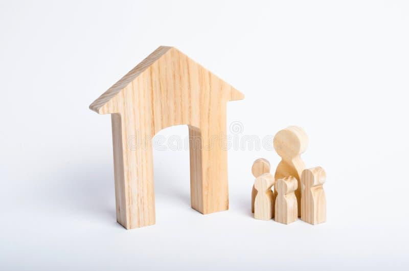 Οι νέοι γονείς και ένα παιδί στέκονται κοντά στο σπίτι τους Έννοια της ακίνητης περιουσίας, που αγοράζει και που πωλεί ένα σπίτι  στοκ φωτογραφία με δικαίωμα ελεύθερης χρήσης