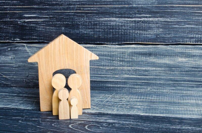 Οι νέοι γονείς και ένα παιδί στέκονται κοντά στο σπίτι τους Έννοια της ακίνητης περιουσίας, που αγοράζει και που πωλεί ένα σπίτι  στοκ εικόνα με δικαίωμα ελεύθερης χρήσης