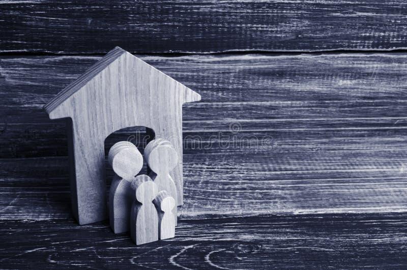 Οι νέοι γονείς και ένα παιδί στέκονται κοντά στο σπίτι τους Έννοια στοκ εικόνες