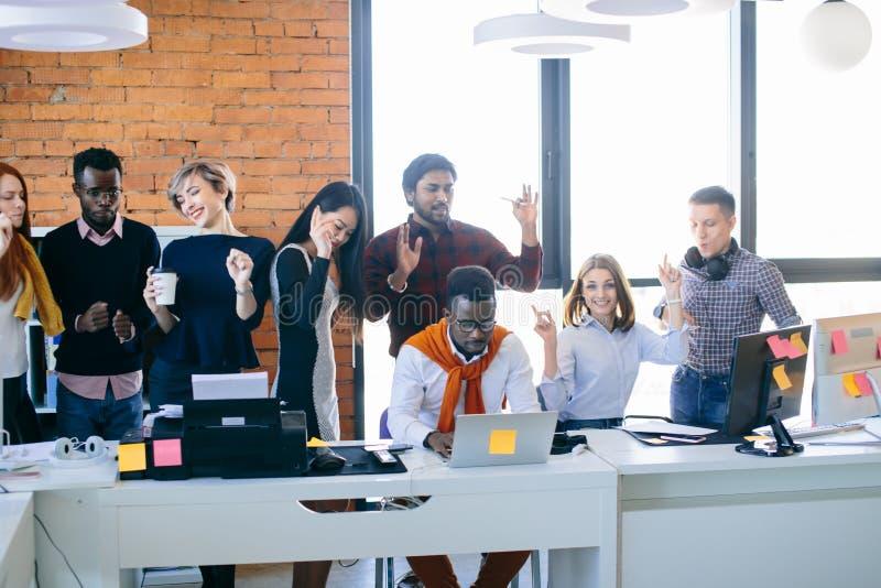 Οι νέοι διαφορετικοί επιχειρηματίες έχουν το κόμμα στον εργασιακό χώρο στοκ εικόνα
