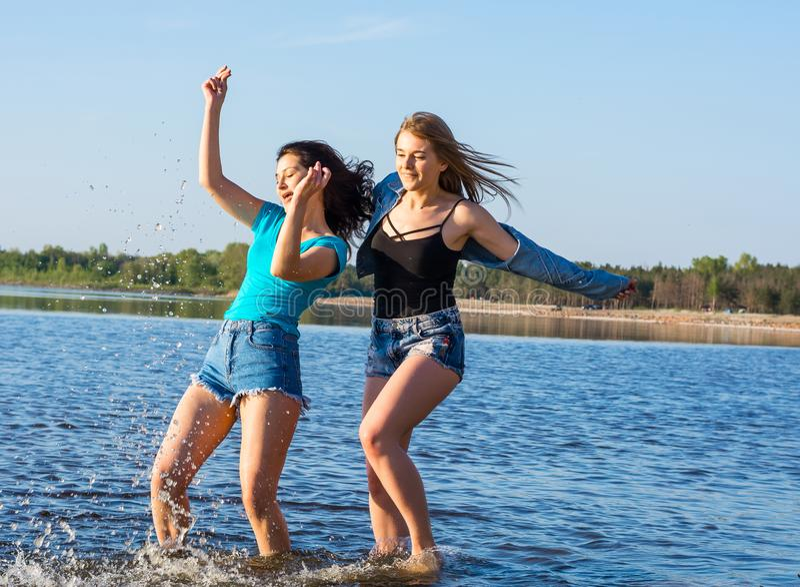 Οι νέοι, δύο γυναίκες, σπουδαστές είναι ευτυχείς στην παραλία στοκ φωτογραφία με δικαίωμα ελεύθερης χρήσης