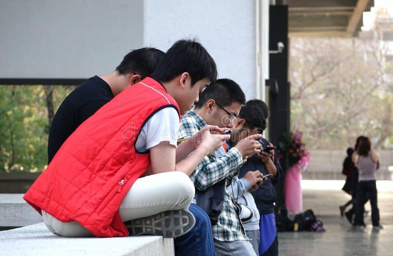 Οι νέοι είναι πολυάσχολοι με το Smartphones τους στοκ φωτογραφία