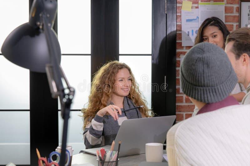 Οι νέοι επιχειρηματίες καυκάσιοι και Ασιάτης συναντιούνται με την ομάδα στοκ εικόνες