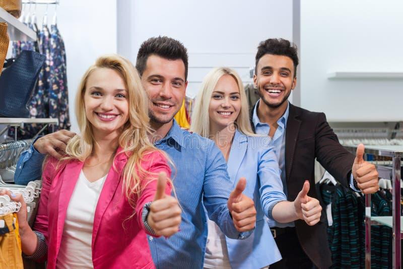Οι νέοι διαμορφώνουν το κατάστημα, ευτυχής αντίχειρας εκμετάλλευσης δύο ζεύγους χαμόγελου επάνω στους πελάτες στοκ φωτογραφία με δικαίωμα ελεύθερης χρήσης