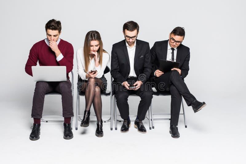 Οι νέοι κάθονται σε μια σειρά στο επιχειρησιακό κέντρο περιμένοντας τη συνέντευξη που απομονώνεται στο λευκό στοκ φωτογραφία με δικαίωμα ελεύθερης χρήσης