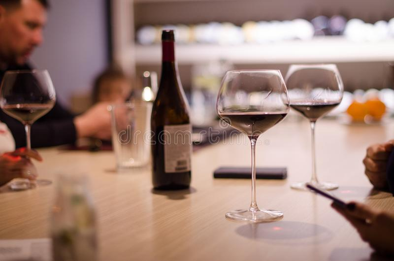 Οι νέοι πίνουν το κόκκινο κρασί από τα όμορφα ποτήρια σε ένα εστιατόριο στοκ φωτογραφία