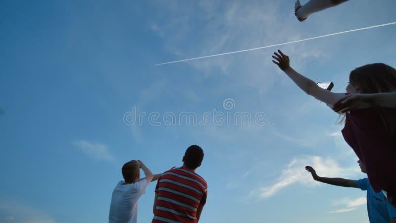 Οι νέοι τύποι και ένα κορίτσι κυματίζουν τα χέρια τους στο αεροπλάνο στον ουρανό στοκ εικόνες με δικαίωμα ελεύθερης χρήσης