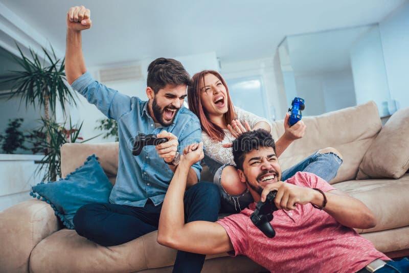Οι νέοι φίλοι παίζουν τα τηλεοπτικά παιχνίδια μαζί στο σπίτι στοκ φωτογραφίες με δικαίωμα ελεύθερης χρήσης