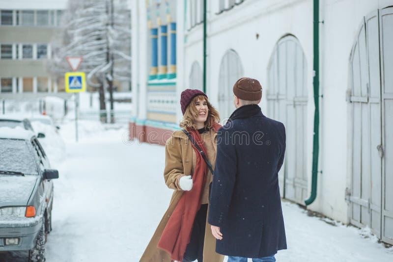 Οι νέοι όμορφοι εραστές ζευγών που αγκαλιάζουν, γελώντας και έχουν έναν χειμώνα διασκέδασης σε μια χειμερινή πόλη χιονιού Χειμερι στοκ εικόνα