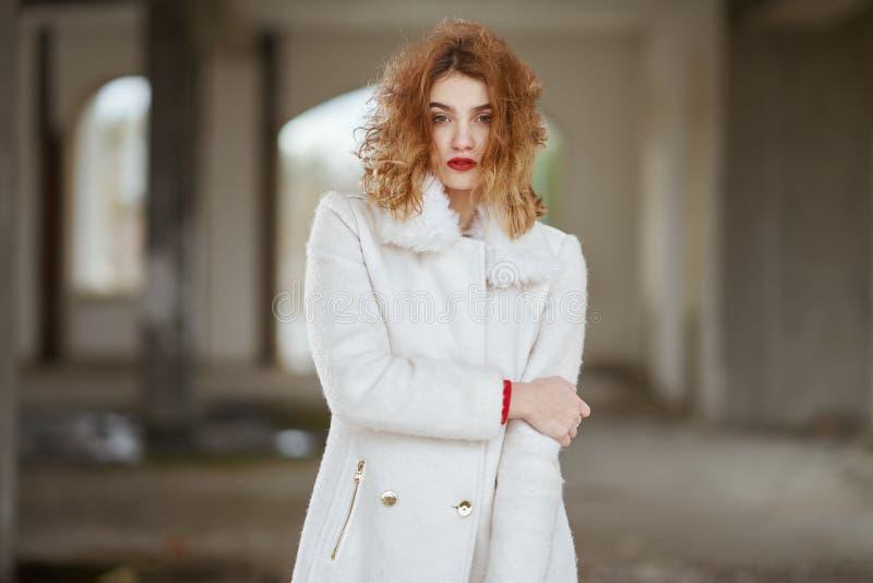 Οι νεολαίες έντυσαν fashionably το κοκκινομάλλες κορίτσι με τη σγουρή τρίχα σε μια άσπρη τοποθέτηση παλτών, εξετάζοντας τη κάμερα στοκ φωτογραφία με δικαίωμα ελεύθερης χρήσης