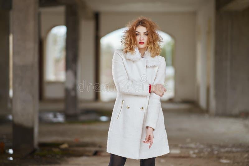 Οι νεολαίες έντυσαν fashionably το κοκκινομάλλες κορίτσι με τη σγουρή τρίχα σε μια άσπρη τοποθέτηση παλτών, εξετάζοντας τη κάμερα στοκ φωτογραφίες με δικαίωμα ελεύθερης χρήσης