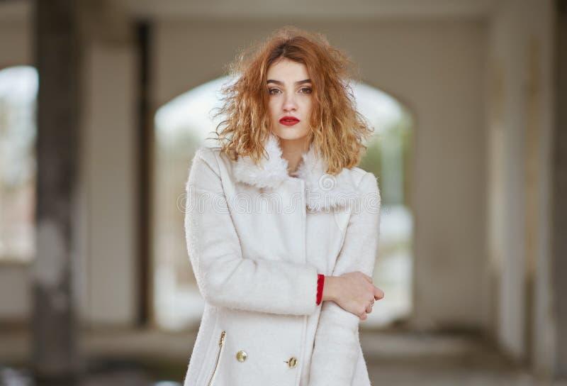 Οι νεολαίες έντυσαν fashionably το κοκκινομάλλες κορίτσι με τη σγουρή τρίχα σε μια άσπρη τοποθέτηση παλτών, εξετάζοντας τη κάμερα στοκ εικόνα με δικαίωμα ελεύθερης χρήσης