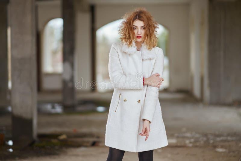 Οι νεολαίες έντυσαν fashionably το κοκκινομάλλες κορίτσι με τη σγουρή τρίχα σε μια άσπρη τοποθέτηση παλτών, εξετάζοντας τη κάμερα στοκ εικόνες