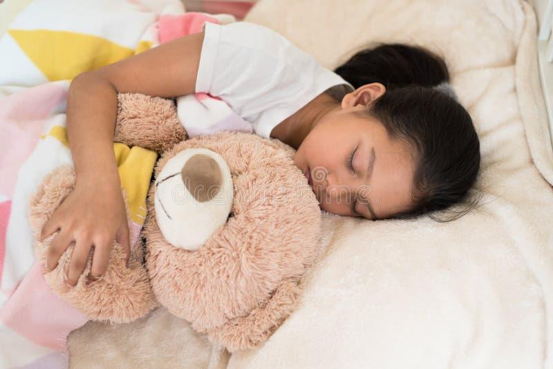 Οι νεολαίες λίγος ασιατικός ύπνος κοριτσιών αγκαλιάζοντας teddy αντέχουν στοκ φωτογραφία με δικαίωμα ελεύθερης χρήσης