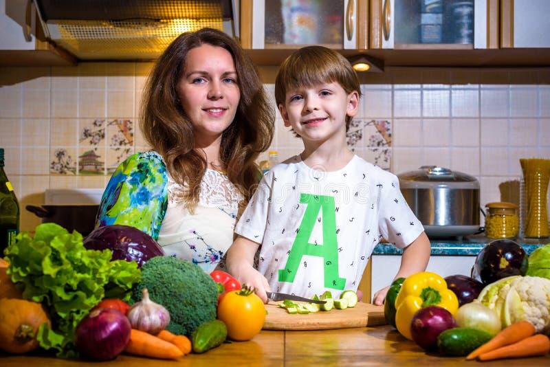 Οι νεολαίες μαγειρεύουν τη μητέρα που στέκεται με την λίγο γιο στην κουζίνα και που αλατίζει τα λαχανικά στοκ εικόνες